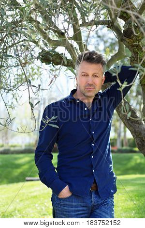 Man in olive grove, image toned. Portrait of handsome mature man lokking at camera over nature background.