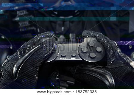 Hands in tactical gloves holding a gamepad with tactical military gear on background and glitch image effect.