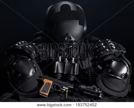 Black military tactical gun, helmet, gloves, cartridge belt, bandolier, gun shell, knife, binocular and knee protection laying on a black table.