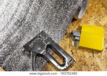 Metal stapler hand tool laying on wooden surface board with pack of clips and insulation roll.