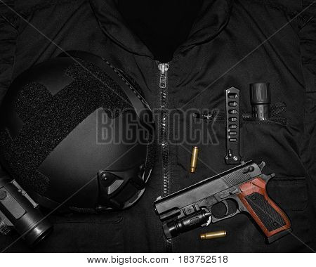 Photo of a tactical helmet, gun shells, hand gun, knife & flashlight  laying on a black swat vest.