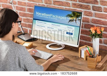 Close-up Of A Woman Filling The Online Vacations Packages Form On Computer