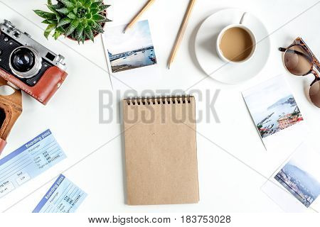 vacation concept with traveller outfit camera, notebook and coffee on white desk background top view