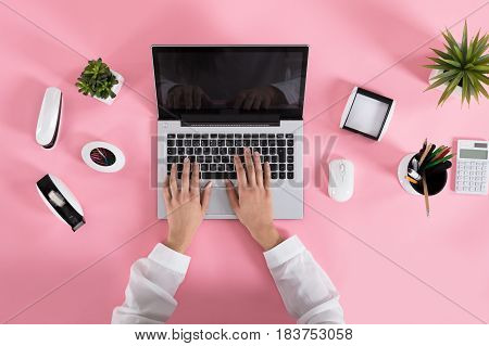 Close-up Of A Woman Using Laptop On Pink Desk At Workplace