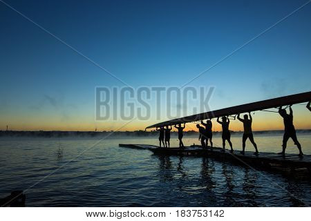 Siluethe of rowers carrying boat during sunrise