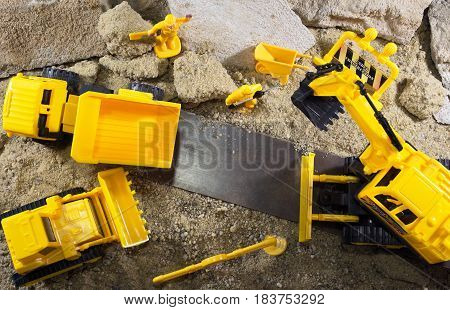 Yellow construction machines and workers standing on sandy & rocky surface upper view.