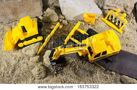 Yellow construction machines standing on sandy & rocky surface upper view.