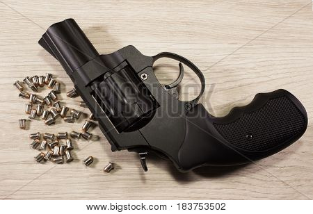 Black metal Flaubert revolver with bullets laying on a bright wooden table.