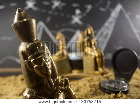 Ancient old pharaoh closeup metal statuettes standing on a sand surface with a blackboard drawn background & compass.