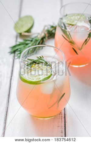 vegetable smoothie with lime pieces and fresh rosemary in glass on white wooden table background