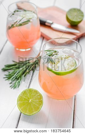 glass of fresh juice with lime, rosemary and knife for healthy drink on white wooden kitchen table background