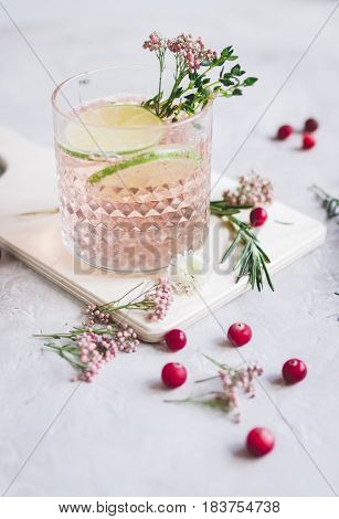 natural nonalcoholic cocktail with berry and cut lime for summer party on stone desk background