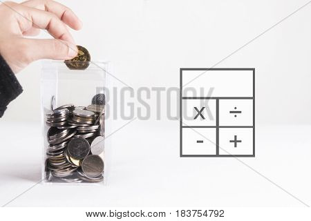 Money saving concept. Hand inserting coin to a transparent, square shaped bank.