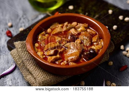 closeup of an earthenware bowl with spanish callos, a typical stew with beef tripe and chickpeas, on a rustic wooden table
