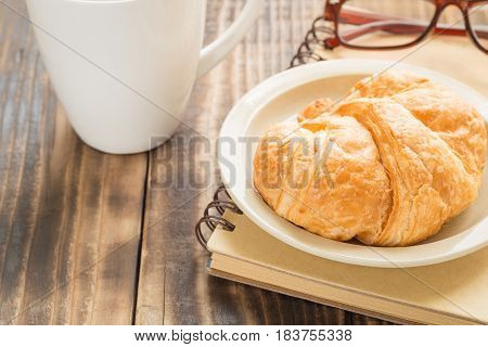 Croissant on a plate on old wooden table