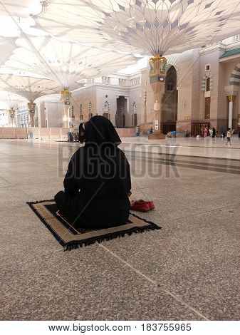 MADINAH, SAUDI ARABIA - AUGUST 20: A women performing prayer at Prophet Muhammad Mosque on August 20, 2015 in Madinah, Saudi Arabia.