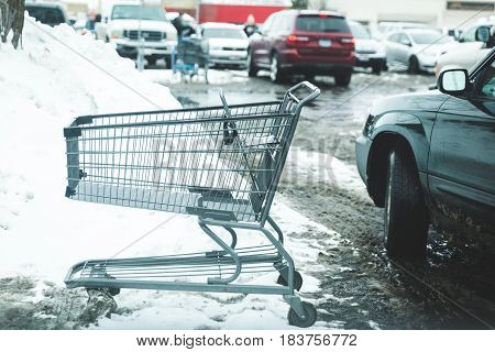Shopping cart in a snowy store parking lot with cars nearby.