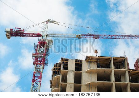 Construction site of multistore building with tower cranes and blue sky. Perspective view