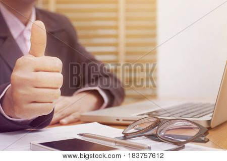 Business woman thumbs up while working with laptop computer.