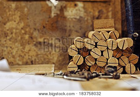 Woodworker`s stuff.Nuts,bolts and a small pile of wooden sticks.