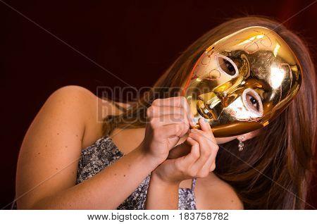 Happy beautiful woman wearing a golden mask.