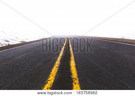 Double yellow line leading off into foggy distance on a remote highway.