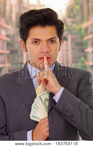 Politician in dark suit and with tie putting money in his suit.