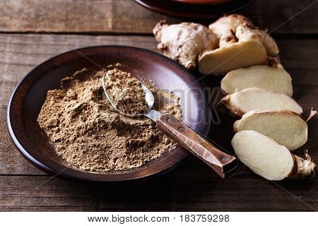 Ground Ginger And Fresh Ginger Root On Cutting Board