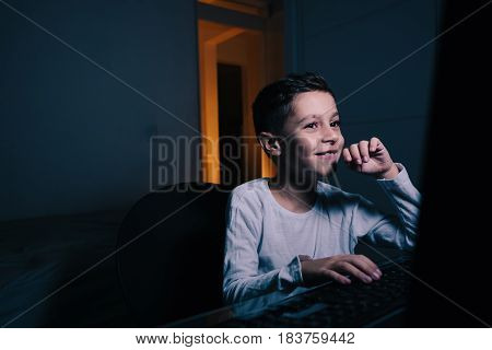 Little Boy Using Computer At Night In Bedroom