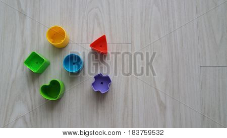 Plastic geometric pieces on gray wooden background
