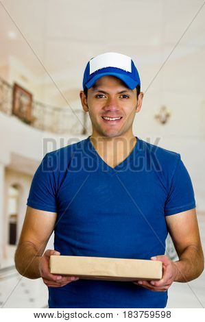 Handsome guy holding a box with a blue uniform