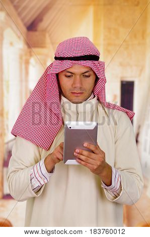 Cute young arabian man using his Tablet.