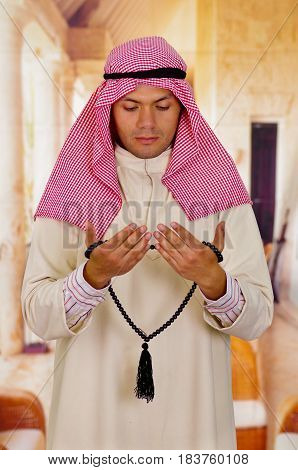 Cute young arabian guy praying to god while holding a masbaha.