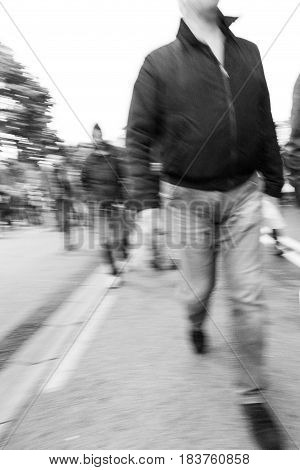 Dangerous group of people walking towards the camera eye. Demonstration. Converted to black and white grain added.