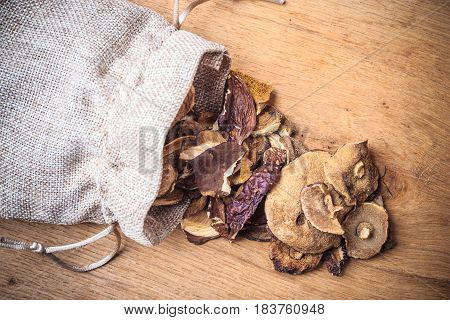 Food. Closeup dry mushrooms spilling out from burlap sack on wooden surface table background.