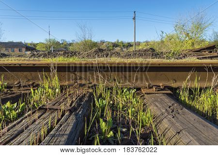 Steel rails bolted down to wooden railroad ties. Old rustic railroad track.