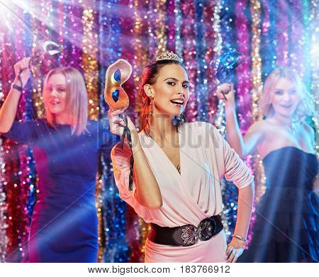 Young excited woman having party and holding carnival masks