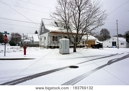 HARBOR SPRINGS, MICHIGAN / UNITED STATES - NOVEMBER 23, 2016: A portable toilet sits in front of a residential construction site, on the corner of Fourth and Washington Streets, after a November snowstorm.