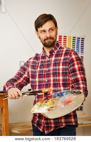 Man artist holds in his hands a paintbrush and a wooden palette with oil paints. Portrait.