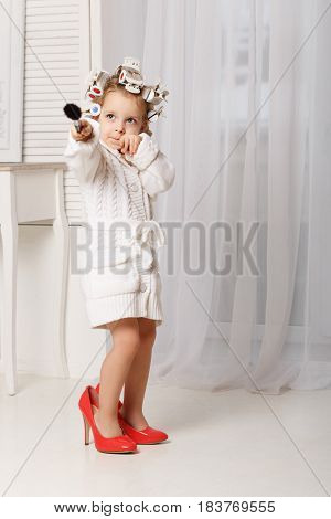 Little girl fashionista. A girl in a curler a robe and red high-heeled shoes is holding a makeup brush. Little coquette posing. Human emotions.