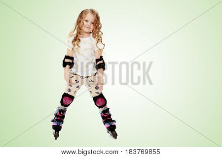 Beautiful, chubby little girl with long, blond, curly hair.Girl riding roller skates in protective gear.On a green gradient background.