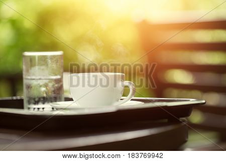 coffee in the morning with water glass cup of espresso on wood table in cafe or coffeeshop.