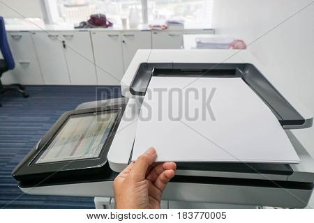 businesswoman put mock up A4 paper sheet on printer feed for scanning