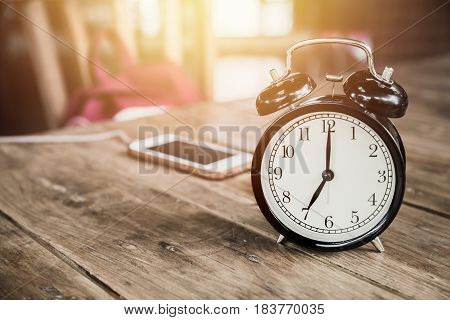 Clock Times At 7 O'clock Morning On Wood Table With Smart Phone Charging At Cafe Blur Background.