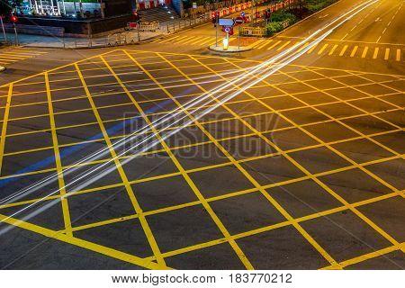 cars driving through yellow no parking area on asphalt street.