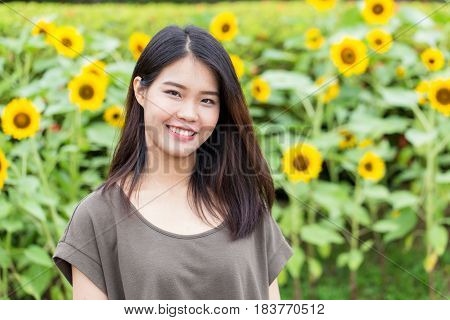 cute portrait asian Thai teen smile with sunflower with copy space.