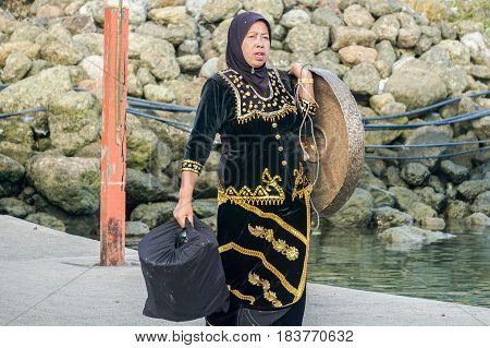 Semporna,Sabah-Apr 22, 2017:Sea Bajau woman of Semporna with percussion set called Kulintangan during Regata Lepa Lepa in Semporna, Sabah. Its providing the main melodic line & played by women.
