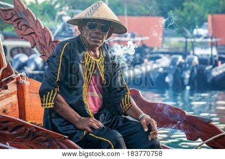 Semporna,Sabah-Apr 22,2017:Sea Bajau man smoking cigarette surrounded by smoke with traditional costume during Regata Lepa Lepa in Semporna,Sabah.Lepa means Boat in the dialect of Sea Bajau people