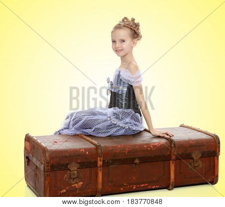 Beautiful little girl in a long Princess dress , sitting on an old road suitcase.On a yellow gradient background.