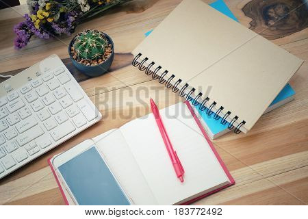 Blank notebook with flower on vintage wooden table. View from above with copy space